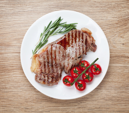 Sirloin steak with rosemary and cherry tomatoes on a plate. View from above photo
