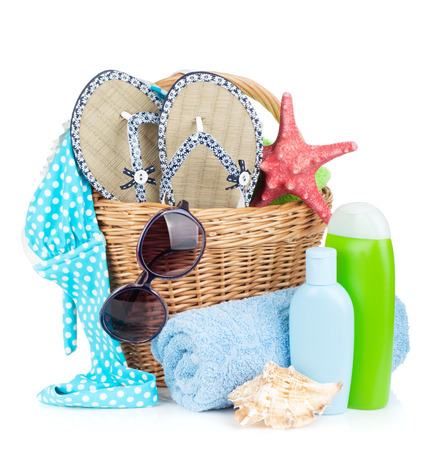 Beach items in basket. Isolated on white background photo