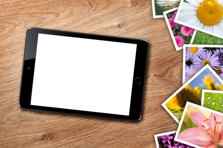 Tablet with blank screen and stack of printed pictures collage on wooden table photo