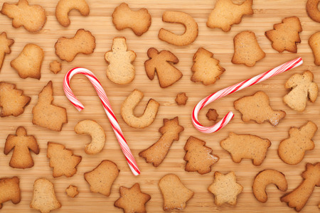 Various gingerbread cookies with candy cane on wooden table background photo