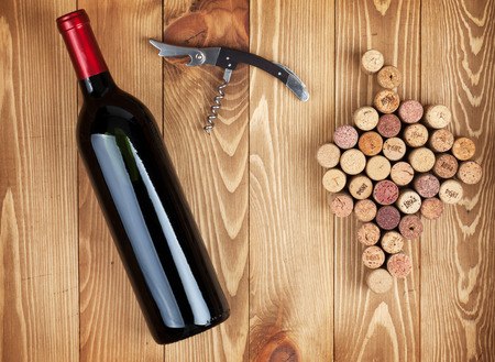 closed corks: Red wine bottle, corkscrew and grape shaped corks on wooden table background