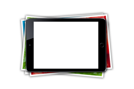 Tablet with blank screen and stack of printed pictures collage. Isolated on white background photo