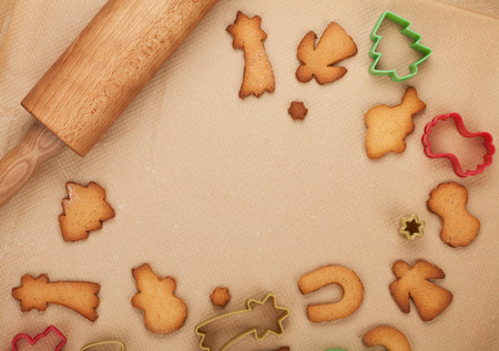 Rolling pin and gingerbread cookies on cooking paper with copy space photo