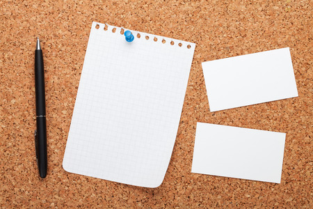cork board: Blank notepad paper, business cards and pen on cork wood notice board Stock Photo