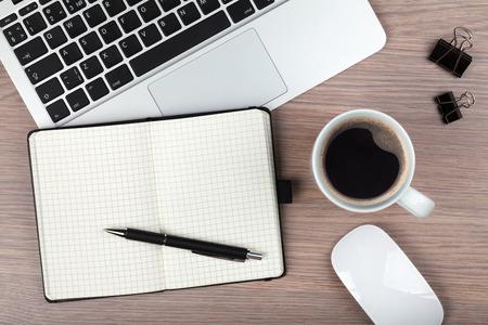 Notepad, Laptop und Kaffeetasse auf Holztisch. Ansicht von oben