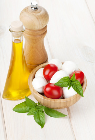 Mozzarella cheese with cherry tomatoes, basil and olive oil with pepper shaker on white wood table photo