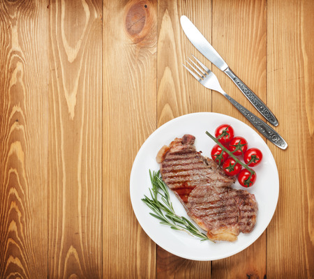Sirloin steak with rosemary and cherry tomatoes on a plate. View from above with copy space photo