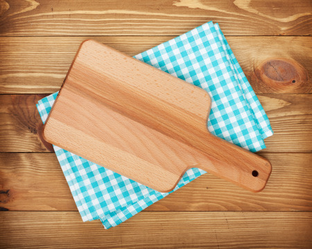 Cutting board over kitchen towel on wooden table background Stok Fotoğraf