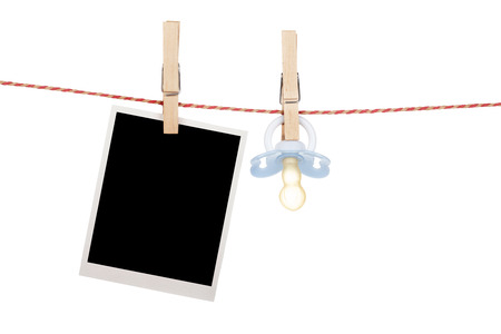 Instant photo and pacifier hanging on the clothesline. Isolated on white background photo