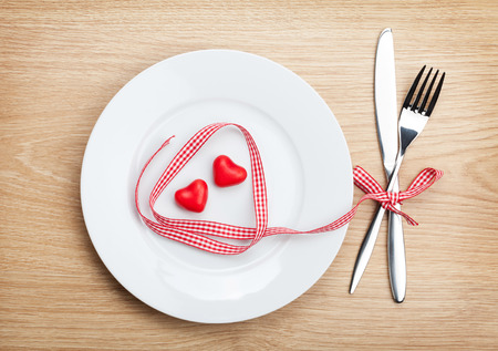 Valentines Day heart shaped red ribbon over plate with silverware. On wooden table background photo