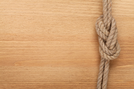 western border: Ship rope knot on wooden texture background