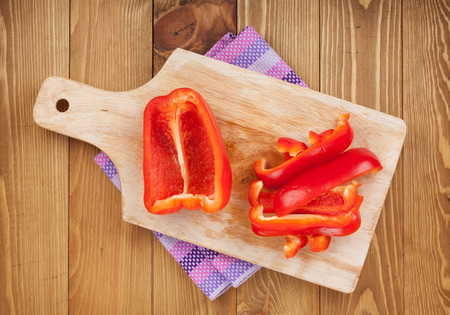 chopping: Red bell pepper on cuting board over wooden table