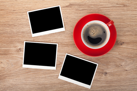 Cup of coffee and three photo frames on wooden table photo