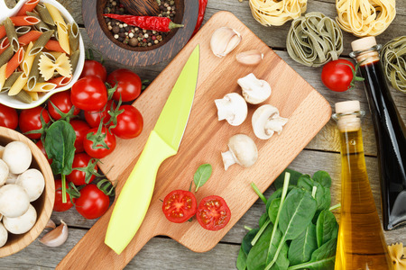 Fresh ingredients for cooking: pasta, tomato, mushroom and spices over wooden table background photo