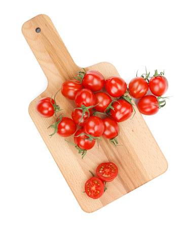 Cherry tomatoes on cutting board. View from above. Isolated on white background photo