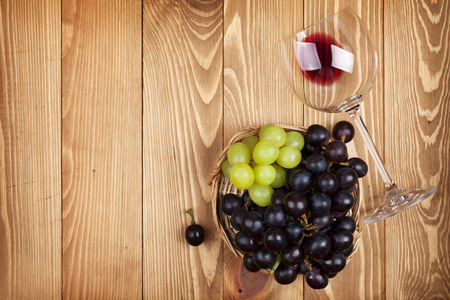 Red wine glass and grape on wooden table background with copy space photo