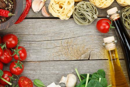 Verse ingrediënten voor het koken: pasta, tomaten en kruiden over houten tafel achtergrond met kopie ruimte Stockfoto