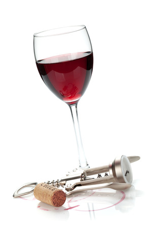 Red wine glass, cork and corkscrew. Isolated on white background photo