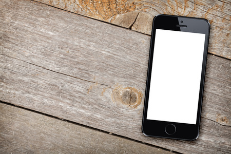 portable phone: Smart phone on wooden table background with copy space Stock Photo