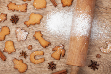 Rolling pin and gingerbread cookies on wooden table photo