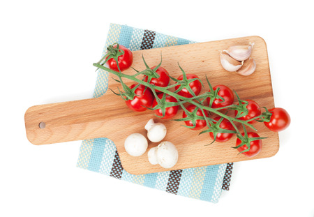 Cherry tomatoes with mushrooms and garlic on cutting board. View from above. Isolated on white photo