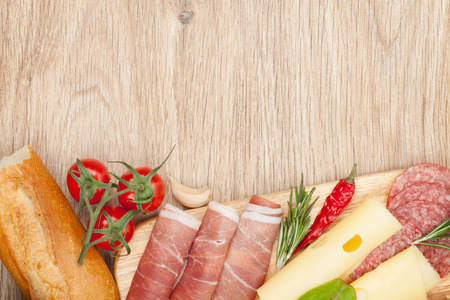 Cheese, prosciutto, bread, vegetables and spices. Over wooden table background with copy space Stock Photo