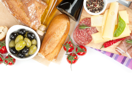 Cheese, prosciutto, bread, vegetables and spices. Isolated on white background with copy space photo