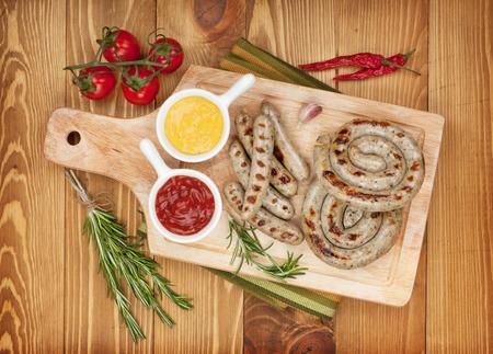 chorizos asados: Salchichas a la parrilla con salsa de tomate y mostaza. Sobre fondo mesa de madera