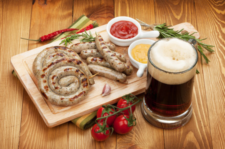 Grilled sausages with ketchup, mustard and mug of beer. Over wooden table background photo