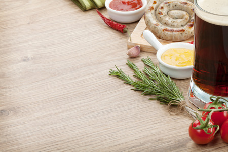 Grilled sausages with ketchup, mustard and mug of beer. Over wooden table background with copy space photo