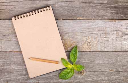 Blank notepad for copy space and basil leaves on wooden table photo