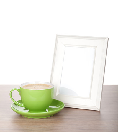 frame and coffee cup on wooden table. Isolated on white  photo