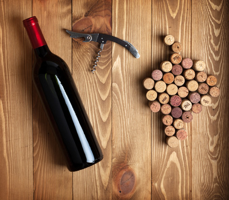Red wine bottle, corkscrew and grape shaped corks on wooden table background photo