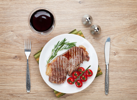 Sirloin steak with rosemary and cherry tomatoes on a plate with wine. View from above photo