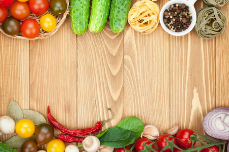 Fresh ingredients for cooking: pasta, tomato, cucumber, mushroom and spices over wooden table background with copy space