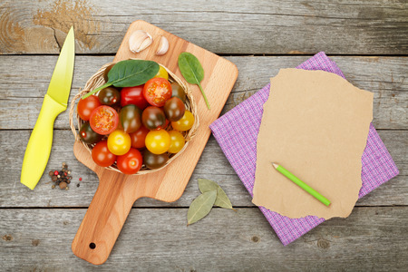 Cherry tomatoes on cutting board over wooden table background with paper for copy space photo