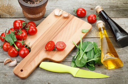 Fresh ingredients for cooking: pasta, tomato, salad and spices over wooden table background with copy space photo