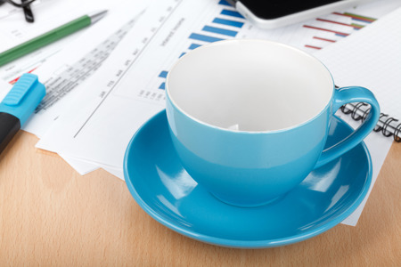 Empty cup on contemporary workplace with financial papers and office supplies photo