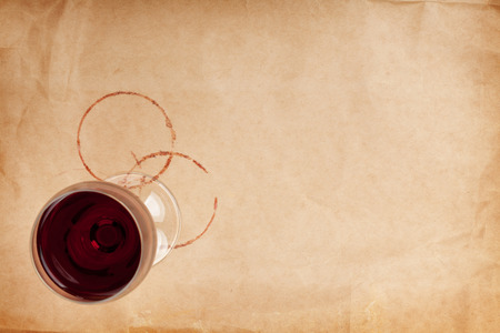 Red wine glass and stains on brown paper background with copy space