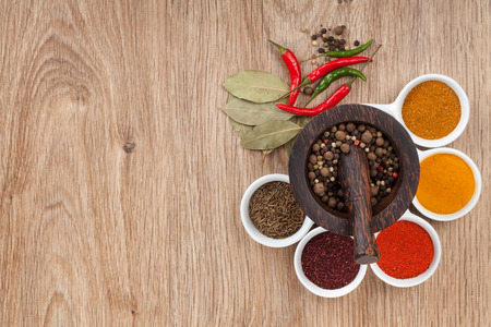 Mortar and pestle with pepper and spices on wooden table photo