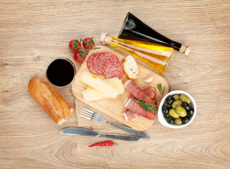 Red wine with cheese, olives, tomatoes, prosciutto, bread and spices. Over wooden table . View from above with copy space photo