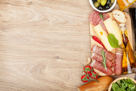 Cheese, prosciutto, bread, vegetables and spices. Over wooden table with copy space photo
