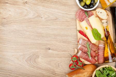 salami: Queso, jamón, pan, verduras y especias. Sobre la mesa de madera con copia espacio