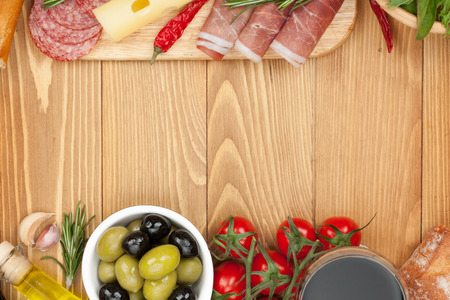 prosciutto: Red wine with cheese, olives, tomatoes, prosciutto, bread and spices. Over wooden table background. View from above with copy space
