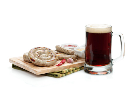 Grilled sausages with ketchup, mustard and mug of beer. Isolated on white  photo