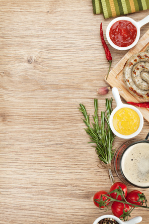 Grilled sausages with ketchup, mustard and mug of beer. Over wooden table with copy space photo