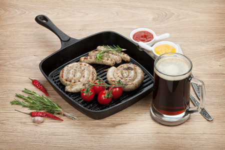 Grilled sausages with ketchup, mustard and mug of beer. Over wooden table  photo