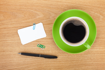 Blank business cards over office table with coffee cup and supplies photo