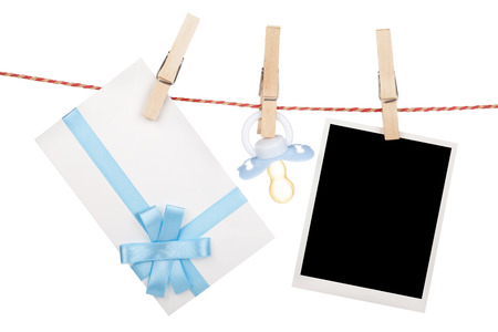 studio picture: Instant photo, gift letter and pacifier hanging on the clothesline. Isolated on white background
