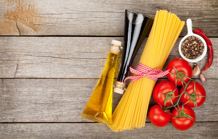 ribbon pasta: Pasta, tomatoes and spices on wooden table background with copy space